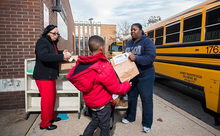Teachers hand out bags of food to students at Sharp Leadenhall Elementary. Photo by Mike Morgan
