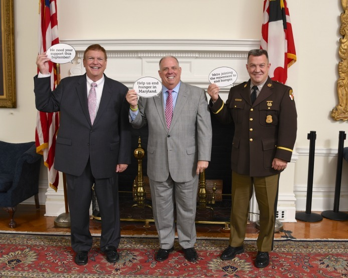 Maryland Transportation Secretary Pete Rahn, Governor Larry Hogan, and Maryland State Police Superintendent Colonel William M. Pallozzi show their support for Hunger Action Month