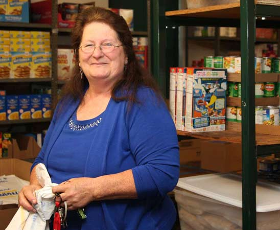 Marge B smiles in while sorting canned goods at the Maryland Food Bank