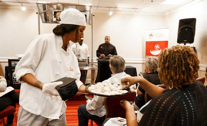 FoodWorks student serves food to a woman.