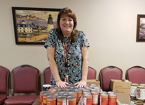 woman standing at tables with canned food