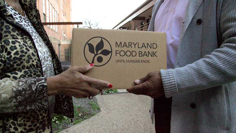 handing a Maryland Food Bank box to a partner