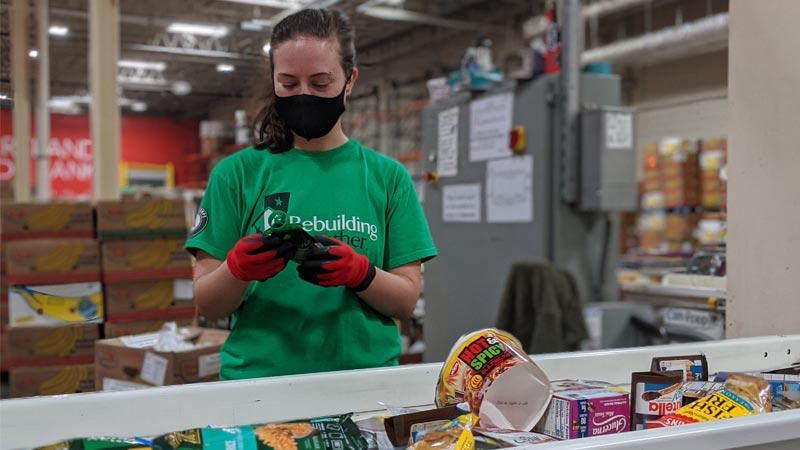 volunteer sorting food at conveyor belt