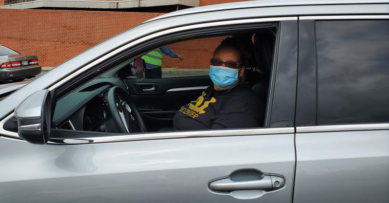 masked woman in car