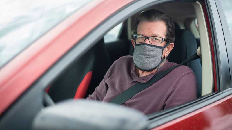masked man in red car