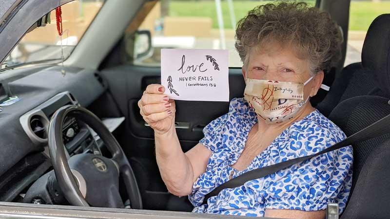 masked woman in car holding card