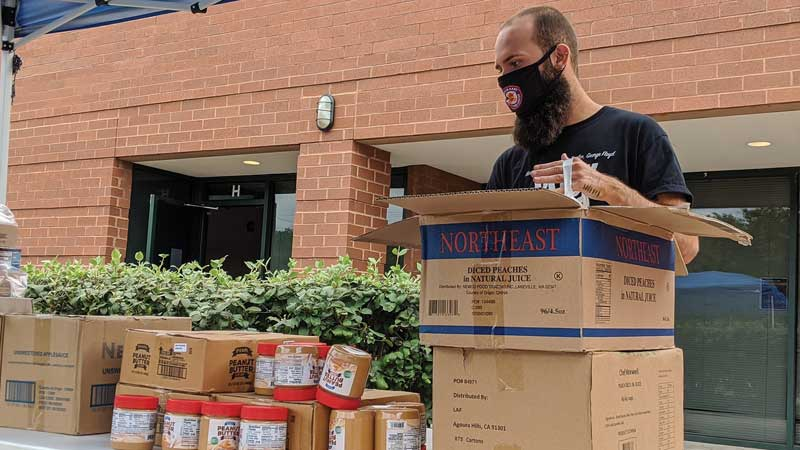 masked man packing boxes outside on a table