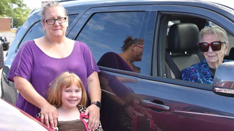 family standing beside grandmother in van