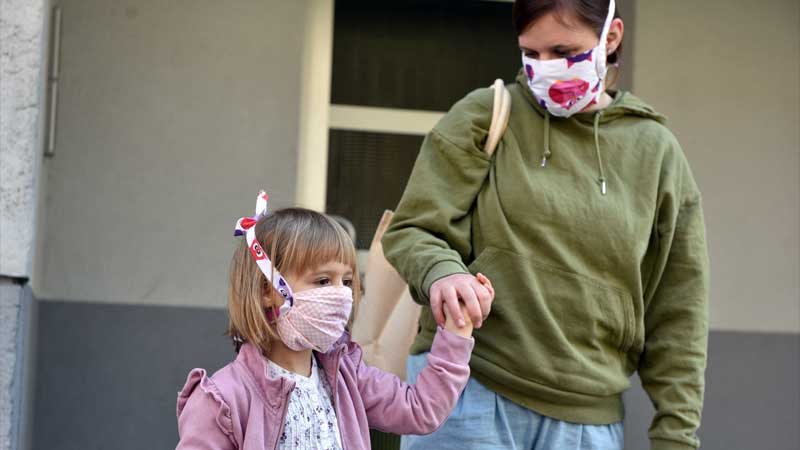 masked mom holding daughter's hand