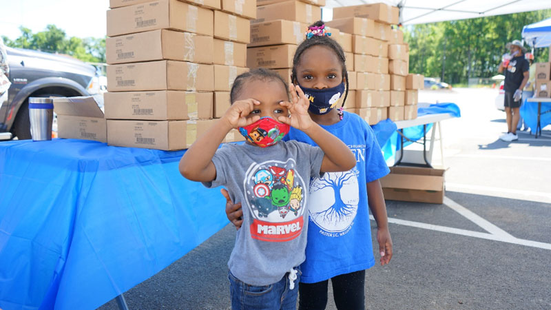 two kids at a food distribution