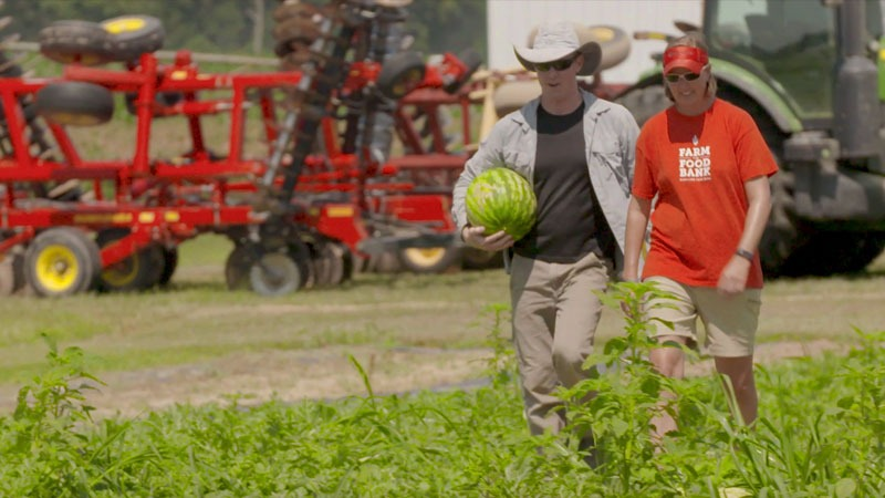 walking on a farm to food bank holding a watermelon