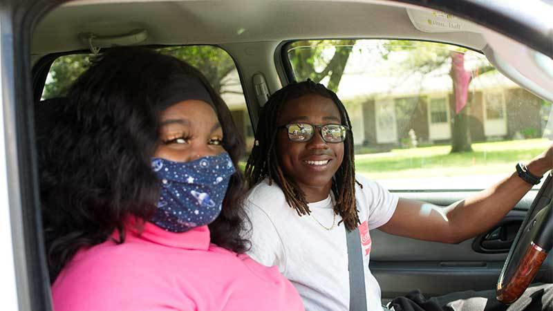 2 masked young adults in car