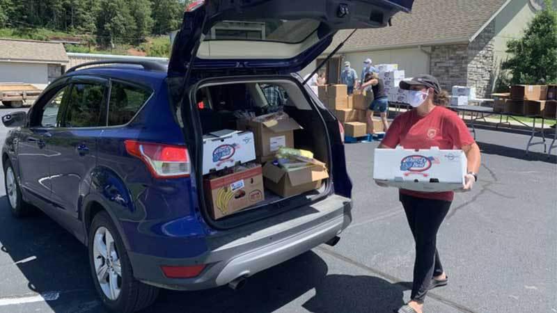 masked volunteer loading box of food into van